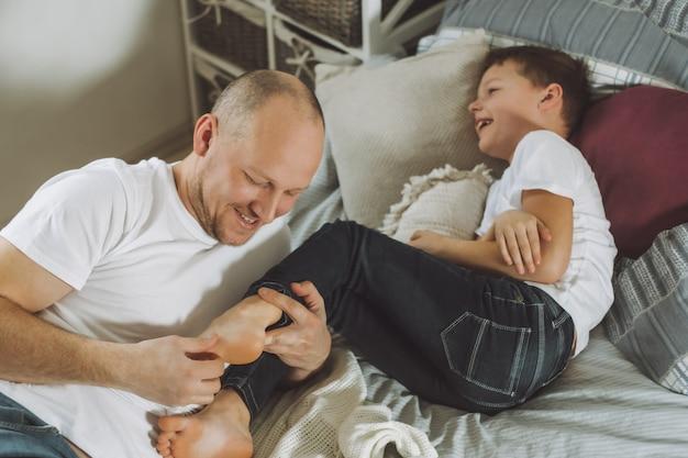 Ojciec bawi się z synem 7-10 na łóżku. tata łaskocze stopy dzieci. rodzina, zabawa