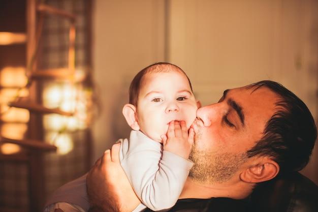 Ojciec bawi się z synem i całuje dziecko trzymając go w ramionach