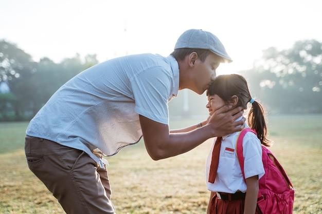 Ojciec całuje córkę w czoło, gdy rano zabiera ją do szkoły