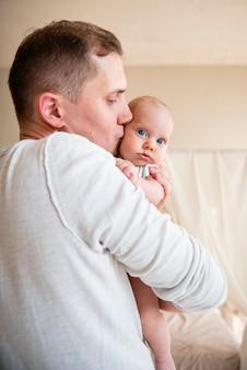 Ojciec całuje noworodka widok z boku