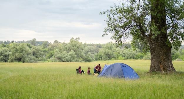 Ojciec, córka i syn siedzą przy namiocie obozowym, przy ognisku i rozmawiają. czas wolny z ojcem, rodzicielstwo. szczęśliwa koncepcja rodziny