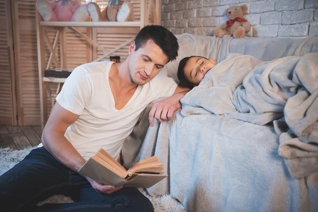 Ojciec czyta książkę z bajkami swojemu śpiącemu synowi.