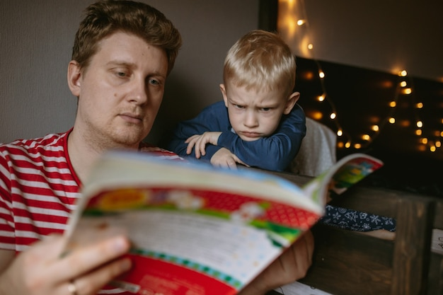 Ojciec czyta świąteczną książkę swojemu uroczemu synkowi świętuje nowy rok wysokiej jakości zdjęcie z ...