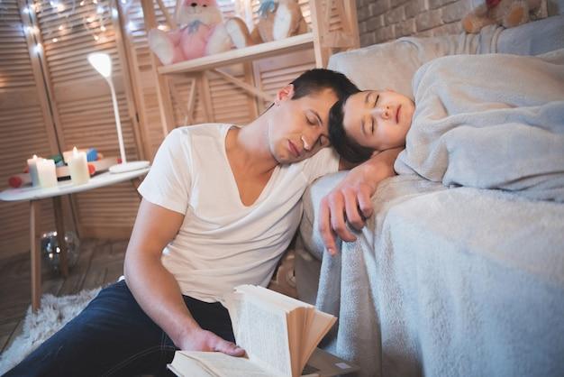 Ojciec czytał książkę synowi. mężczyzna i chłopiec śpią