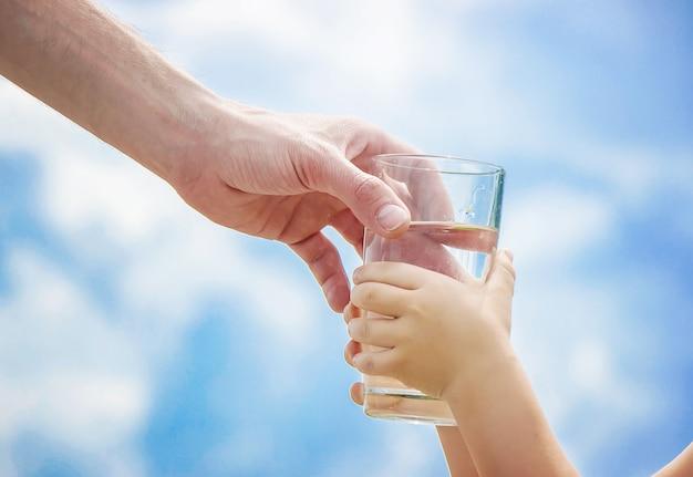 Ojciec daje dziecku szklankę wody. selektywna ostrość.
