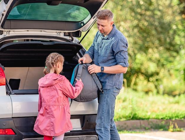 Ojciec daje plecak uczennicy obok otwartego bagażnika samochodu
