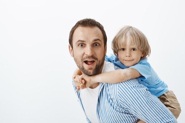 Ojciec daje przejażdżkę na barana słodkiemu blond synowi z bielactwem. portret beztroskiego pięknego taty i dziecka, przytulanie