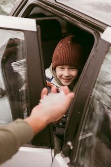 Ojciec daje synowi śnieg podczas wspólnej podróży samochodowej