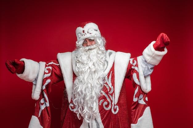 Ojciec frost z długą białą brodą zaprasza do przytulenia, zdjęcie na czerwonej ścianie