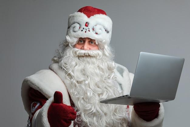Ojciec frost z długą brodą zrobić coś z laptopem, zdjęcie na białym tle na szarej ścianie