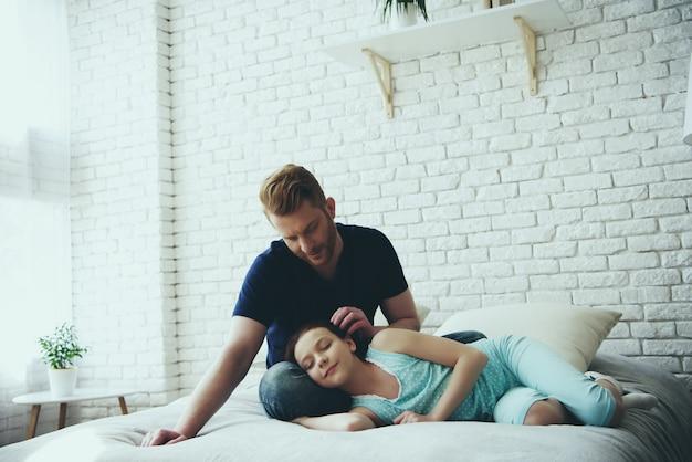Ojciec gładzi włosy córki, dziewczyna śpi.