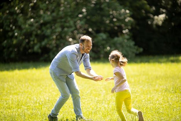 Ojciec goni swoją uroczą córeczkę podczas zabawy w parku