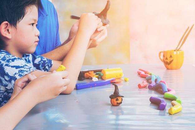 Ojciec gra glinianą zabawkę z dzieckiem