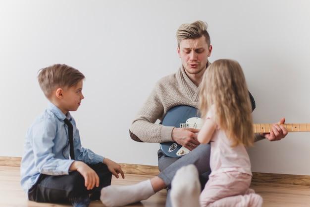 Ojciec gra na gitarze ze swoimi dziećmi