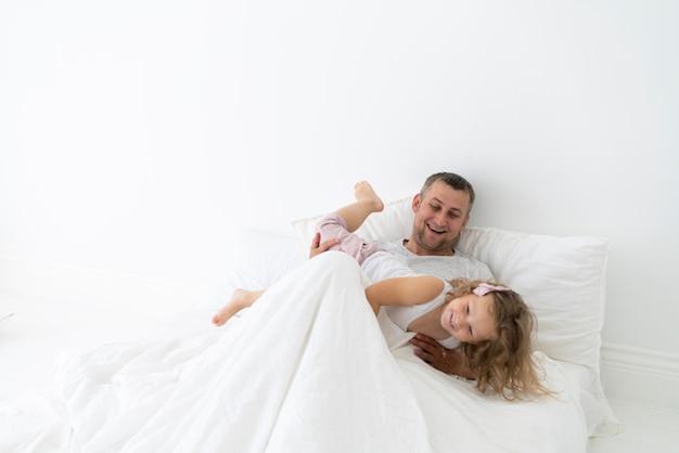 Ojciec gra z córką w sypialni