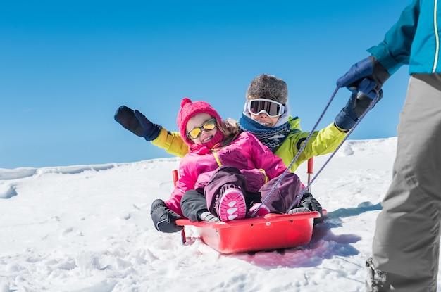 Ojciec gra z dziećmi na śniegu