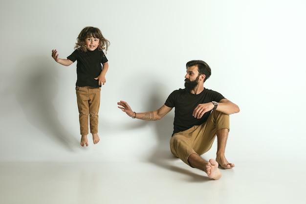 Ojciec gra z młodym synem przed białym