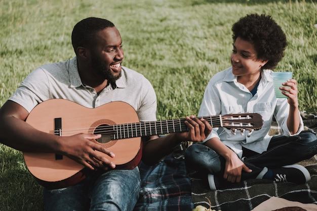 Ojciec grać na gitarze i patrząc na syna na pikniku.