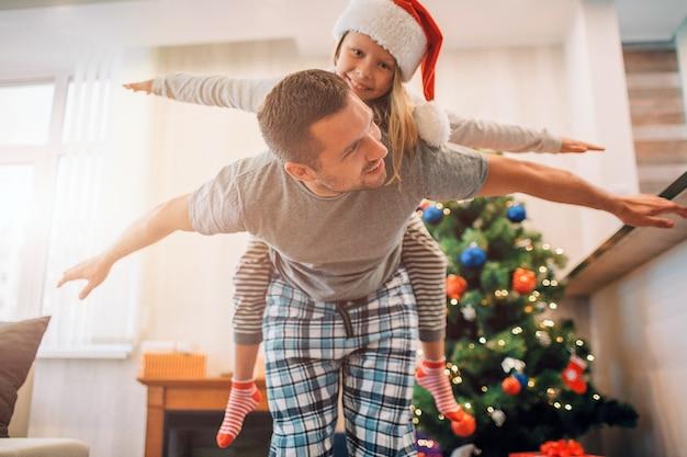 Ojciec i córka bawią się w pokoju. ujeżdża ją na plecach. trzymają ręce z dala od ciała. młody człowiek patrzy na dziewczynę. uśmiechają się.