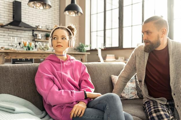 Ojciec i córka. brodaty ojciec przychodzi do córki słuchając muzyki w słuchawkach ze szczerą rozmową