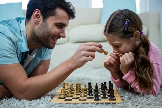 Ojciec i córka gra w szachy w salonie