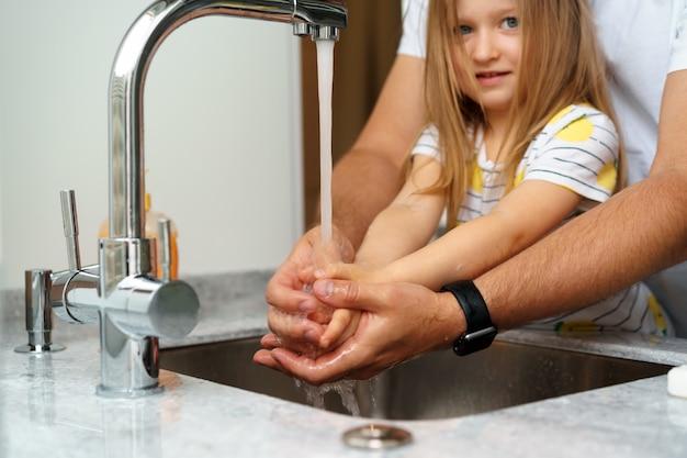 Ojciec i córka myją ręce nad zlewem w kuchni