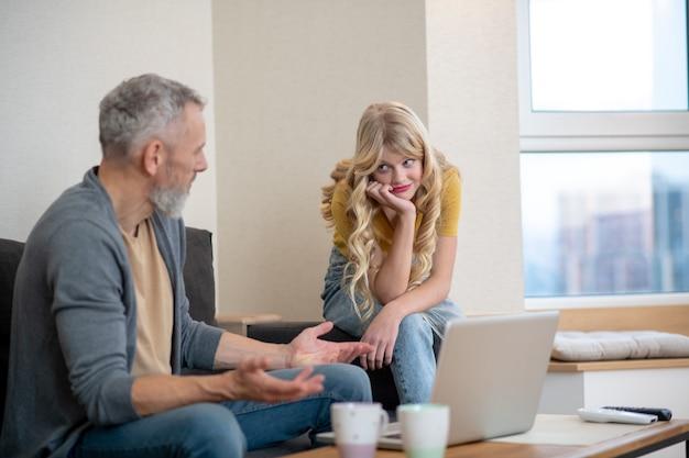 Ojciec i córka oglądają coś na laptopie