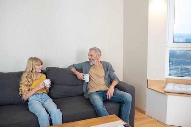 Ojciec i córka. ojciec i córka siedzą na kanapie w domu