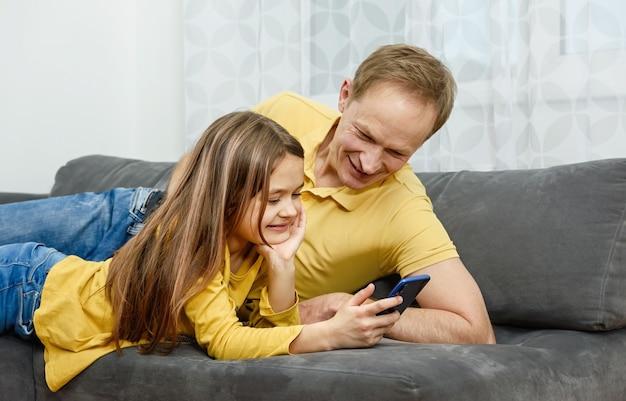 Ojciec i córka patrząc w smartfon i świetnie się bawią. szczęśliwa rodzina koncepcja.