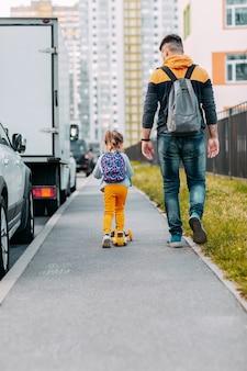 Ojciec i córka po raz pierwszy idą do szkoły. powrót do szkoły po pandemii.