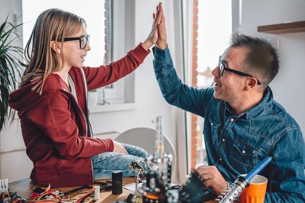 Ojciec i córka pracują nad komponentami elektronicznymi i wiwatują