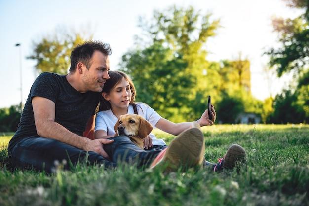 Ojciec i córka relaksuje przy parkiem z psem