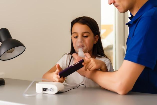Ojciec i córka robią inhalacje. troskliwy tata pomaga córce oddychać przez maskę. leczenie dróg oddechowych.