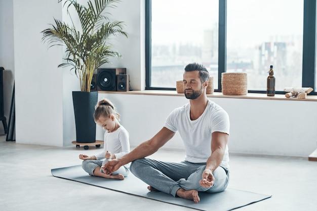 Ojciec i córka robią jogę siedząc w pozycji lotosu w domu