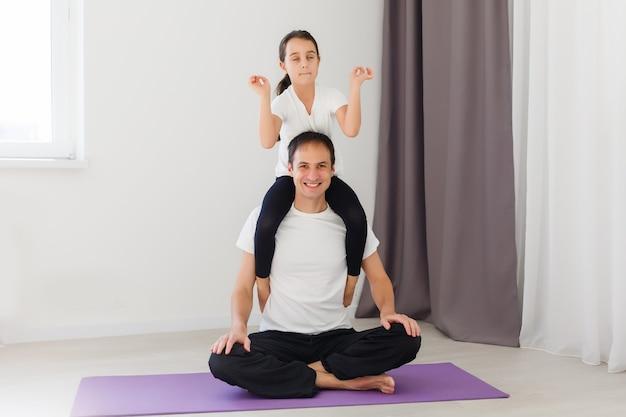 Ojciec i córka robią jogę w domu