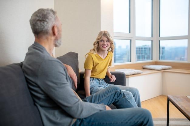 Ojciec i córka siedzą na kanapie w domu