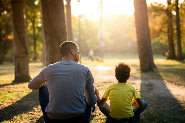 Ojciec i córka siedzą na trawie w parku razem podziwiając zachód słońca