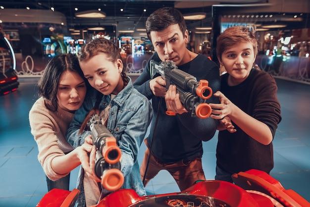 Ojciec i córka strzelają z broni w salonie gier.
