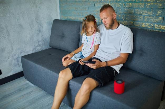 Ojciec i córka testują inteligentny głośnik bezprzewodowy, kontrolują urządzenia domowe za pomocą poleceń głosowych, siedzą na kanapie w domu, koncepcja inteligentnego domu