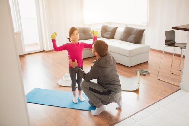 Ojciec i córka trenują w domu. trening w mieszkaniu. sport w domu. stoją na macie do jogi. dziewczyna trzyma hantle.