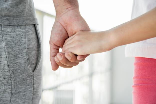 Ojciec i córka trzymając się za ręce