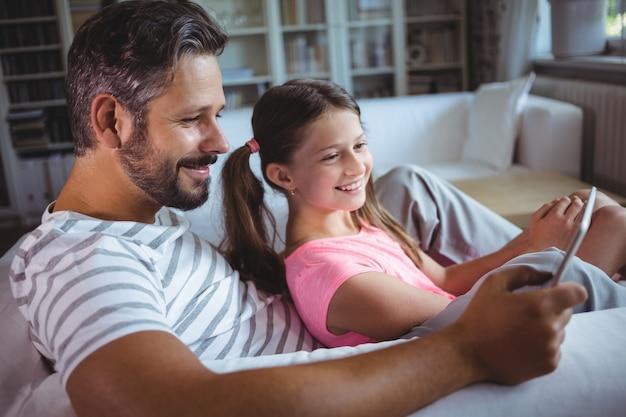 Ojciec i córka używa cyfrową pastylkę w żywym pokoju