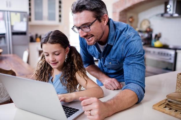 Ojciec i córka używa laptop w kuchni