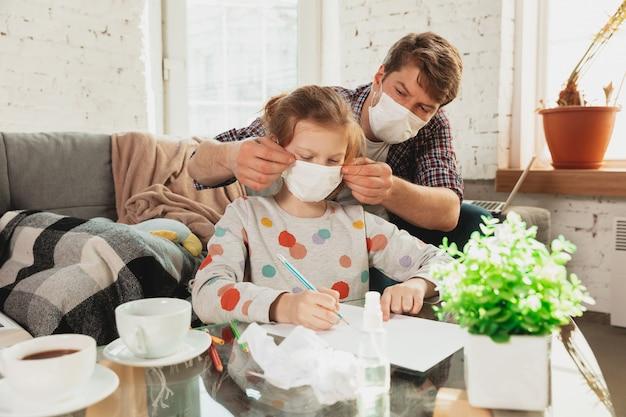 Ojciec i córka w ochronnych maskach i rękawiczkach na białym tle w domu