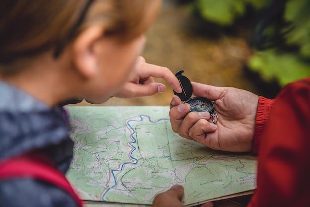 Ojciec i córka wycieczkuje w lesie i sprawdza mapę