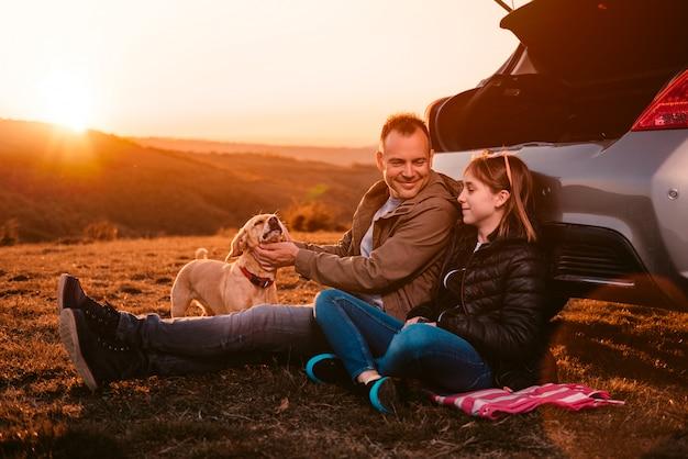 Ojciec i córka z psem siedzi samochodem na wzgórzu