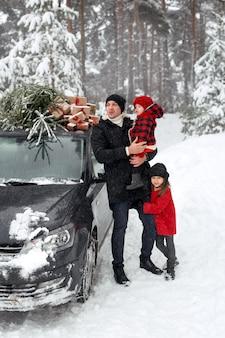 Ojciec i córki przy samochodzie z choinką odwracają wzrok ze zdziwioną miną