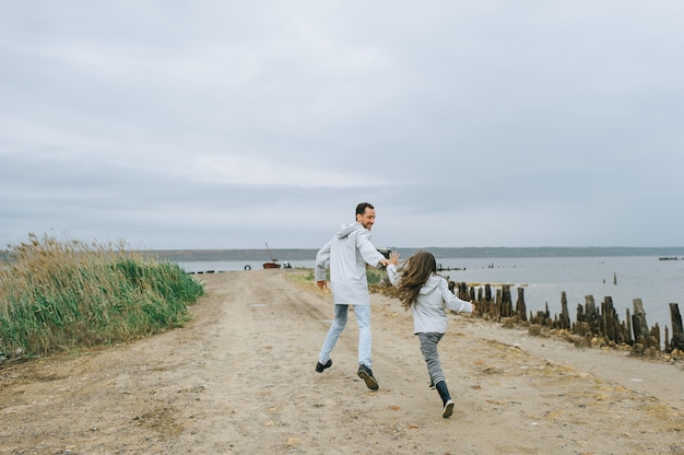 Ojciec i dauther ubierali się w płaszcz przeciwdeszczowy biegnący w pobliżu jeziora i bawili się dobrze