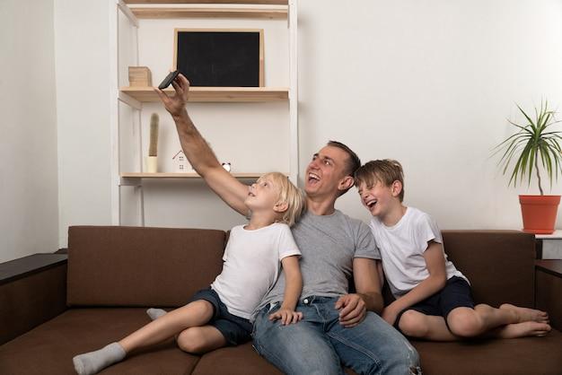 Ojciec i dwaj synowie bawią się i kręcą wideo na smartfonie. wypoczynek z dziećmi.