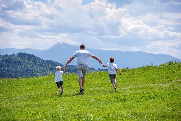 Ojciec i dwóch młodych synów biegnących po zielonym polu, trzymając się za ręce